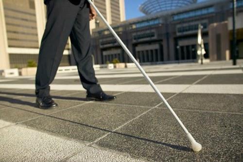 Imagem que mostra apenas as pernas de um homem em traje social, e a sua frente uma bengala, eles estão em uma calçada em um dia ensolarado.