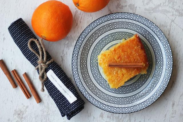 Κομμάτι πορτοκαλόπιτας με ολόκληρα πορτοκάλια