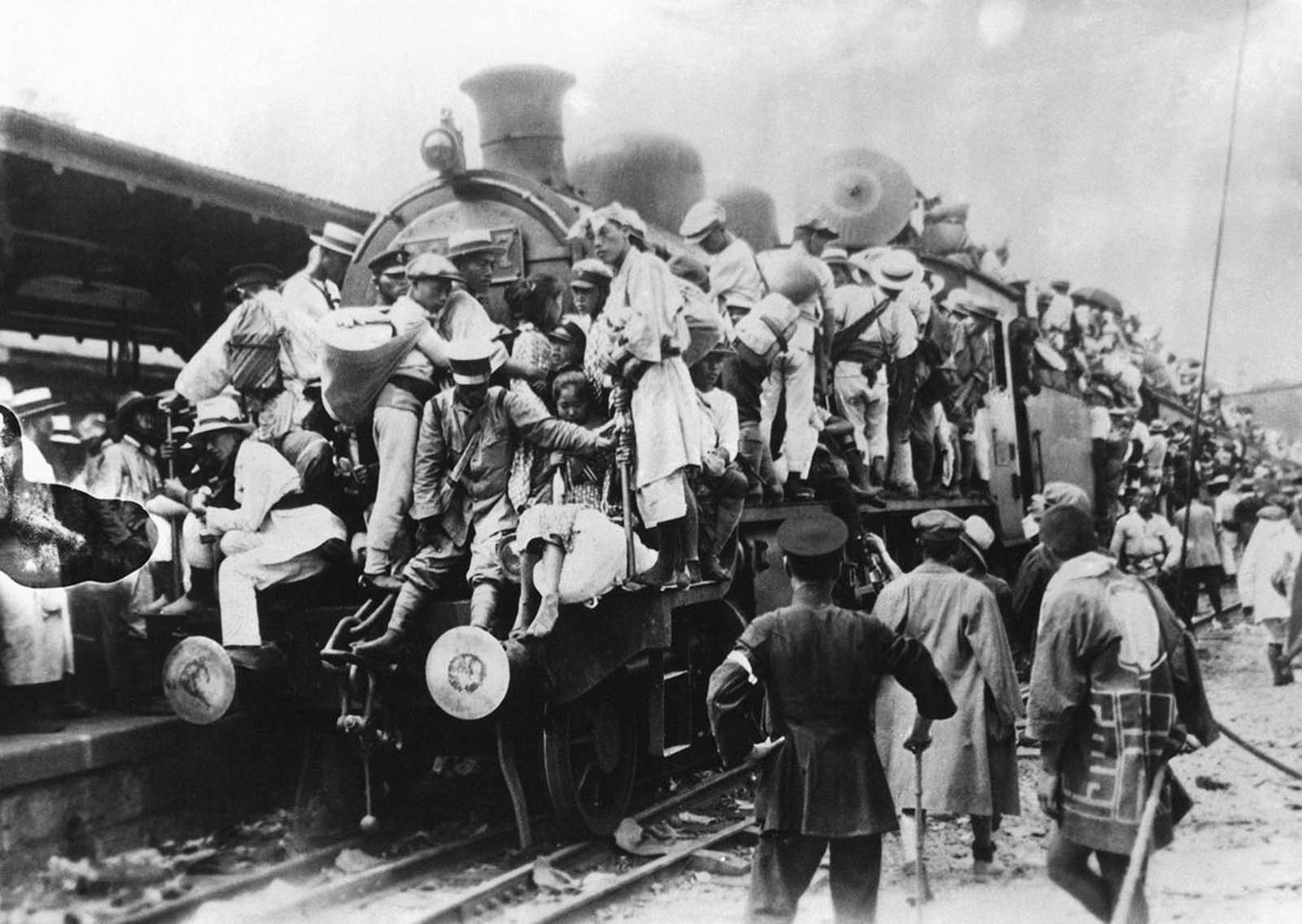 People taking refuge to Japan's countryside climb and clinch to one of few trains leaving the capital in 1923.