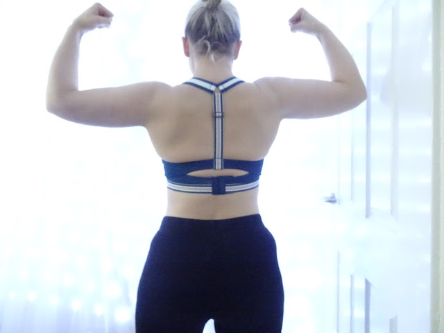 back of woman flexing in sports bra