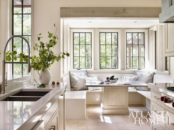 Gorgeous white farmhouse kitchen with black steel windows and banquette