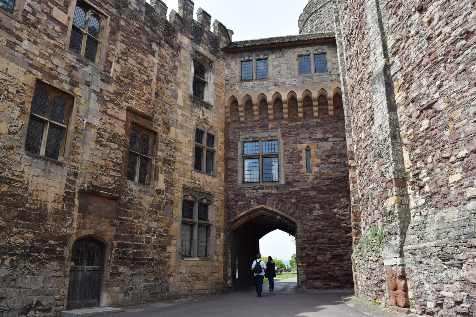 from the courtyard of Berkeley Castle looking up at the old stone walls. directly in front is the entrance to the castle courtyard which I passed through