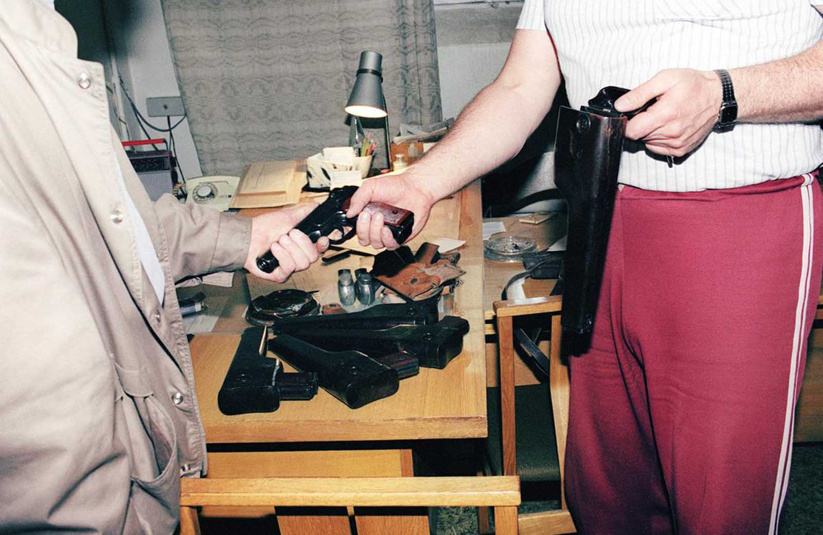 A member of the KGB (right) who requested anonymity hands over his weapon to a Lithuanian official before leaving the KGB headquarters in Vilnius after Lithuanian government decided to drop the Soviet secret service organization, on August 31, 1991.