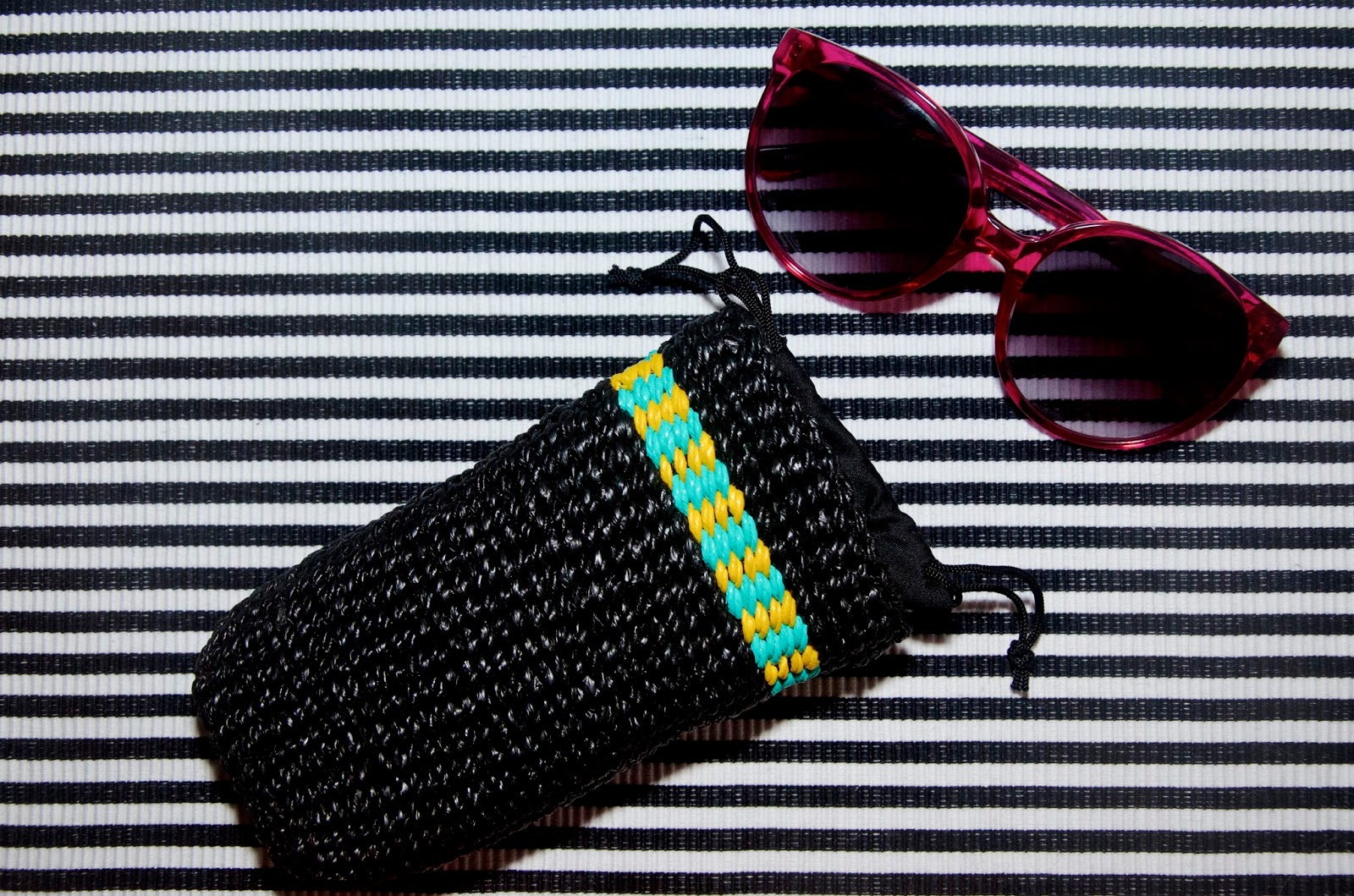 Hot Pink Sunglasses and plastic woven case on striped background
