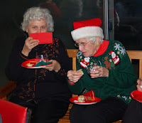 Two women in Christmas sweaters enjoying refreshments and chatting