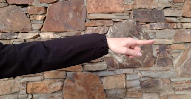 Kiviseinä, musta takki, sormet