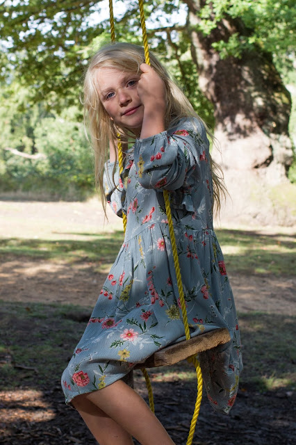 A young blonde girl on a swing in the forest