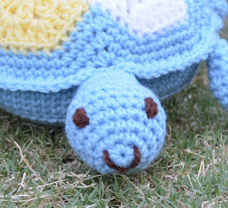 Front view of turtle with a close up of his face which is light blue with eyes and smile embroidered in dark brown 8 ply acrylic yarn. The head is crocheted with a spiral amigurumi technique. The curve of the mouth is in alignment with the curve of the first round of the spiral. The eyes are level with the 4th and 5th rounds.