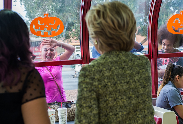 image of a young white woman spying Hillary through the window of a fast food establishment; she is grinning hugely and leaning on the glass