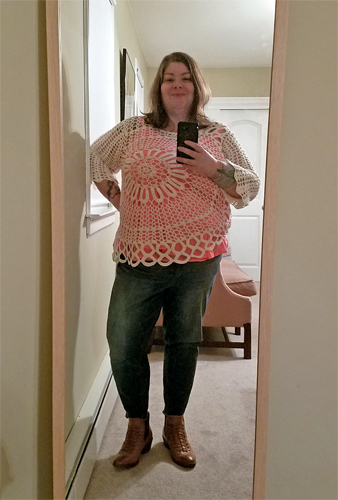 image of me in a mirror, wearing a white crocheted top over a pink cami, ankle-length blue jeans, and brown ankle boots