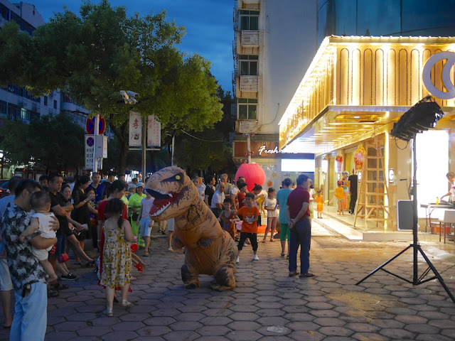 person in inflatable Tyrannosaurus costume entertaining