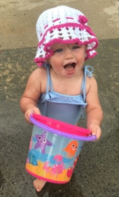 Toddler with a beach bucket and wearing the white and pink crocheted summer hat.