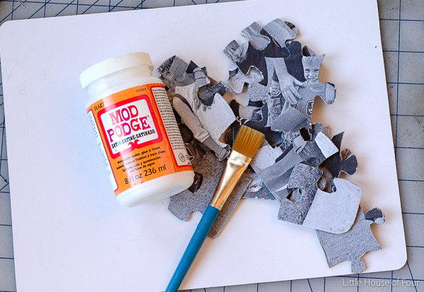 Apply mod podge over cardboard puzzle pieces.
