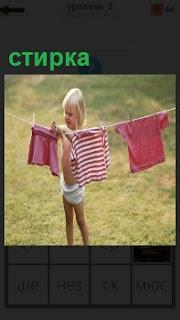 Маленькая девочка на веревки развешивает свое белье после стирки