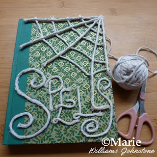 Spells and spiderweb marked onto a hardcover front of book