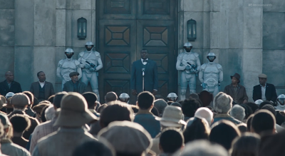 The opening scene of the Catching Fire teaser preview shows an announcement from a man in District 11