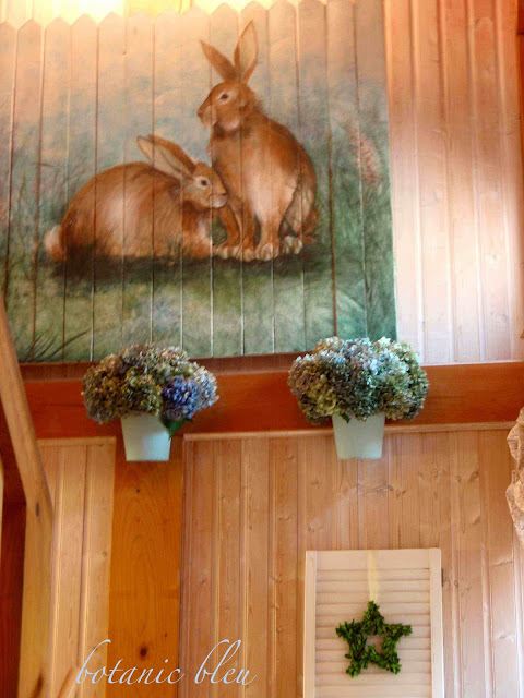Hand painted bunnies on wood planks hang in stairwell