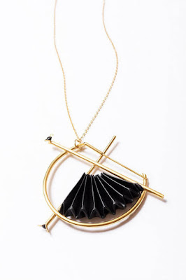 folded black fan in circular golden pendant with necklace chain