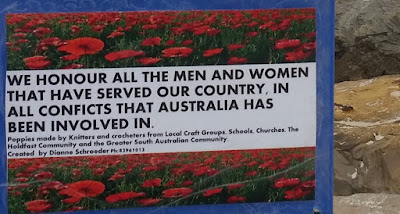 A close-up of the dedication attached to the jetty next to the poppy installations. It has a blue border with a photograph of a field of poppies. A strip of text is in the middle with the following words: We honour all the men and women that have served our country, in all conflicts that Australia has been involved in. Poppies made by knitters and crocheters from local craft groups, schools, churches, the Holdfast community and the greater South Australian community. Created by Dianne Schroeder. Ph: xxxxxxxxxxx [I have purposely not reproduced Dianne's phone number here. If you wish to contact her, please leave a message at the end of this blog post or email jodiebodiecrochets@gmail.com]