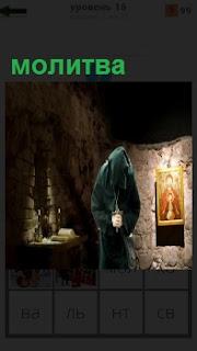 В помещении стоит священник и осуществляет молитву, висит икона на стене