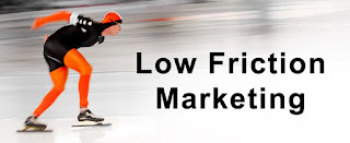 "Ice skater in orange and black quickly moving right with the text ""low friction marketing"" on black letters on the right"
