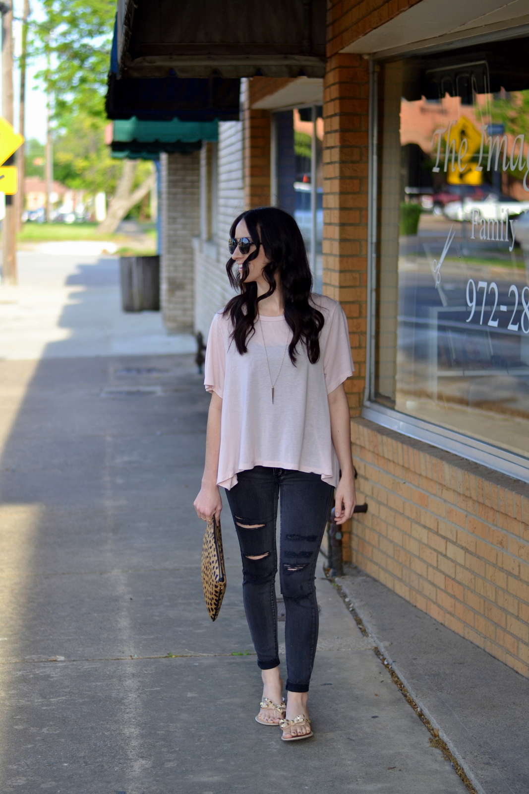 Casual date night idea with a basic tee, distressed jeans and leopard clutch