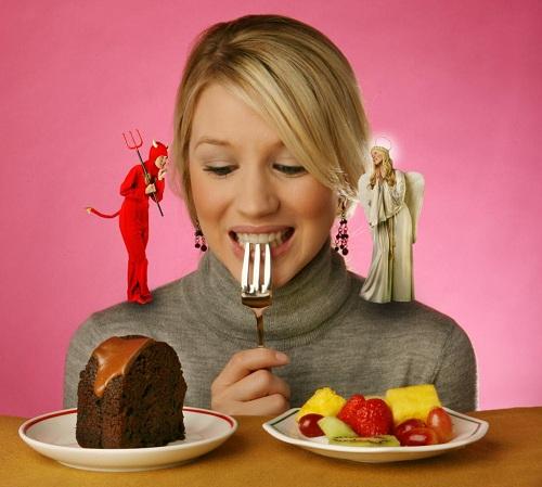 mujer indecisa sobre un plato sano y uno perjudicial