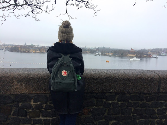 Explorer stood by the river in Stockholm with Kanken backpack