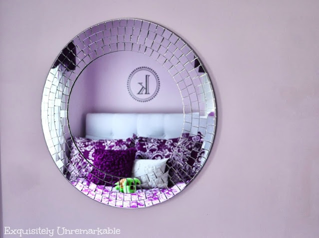Round Mosaic Mirror on a pale purple wall reflecting purple bedding