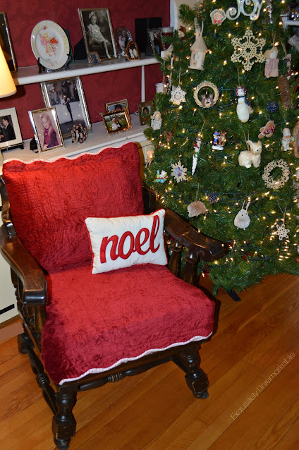 Wooden chair with red velvet shams covering the cushions in front of a bookshelf
