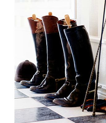 row of peter se carlsson riding boots in a mudroom foyer with checkered floors