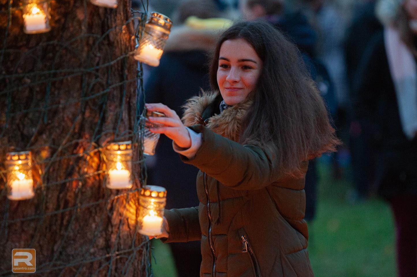 Jaunkundze aizdedzina kokā pakārtu svecīti