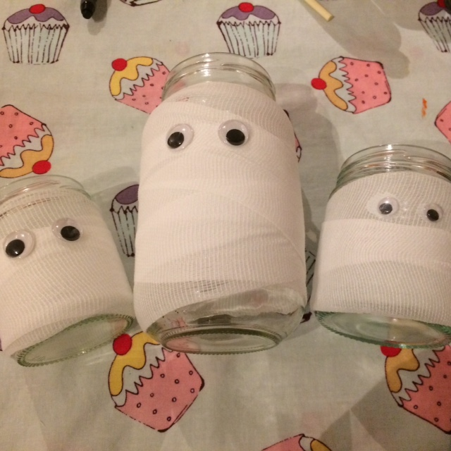 Three jars of different sizes, wrapped in bandages to look like mummy's