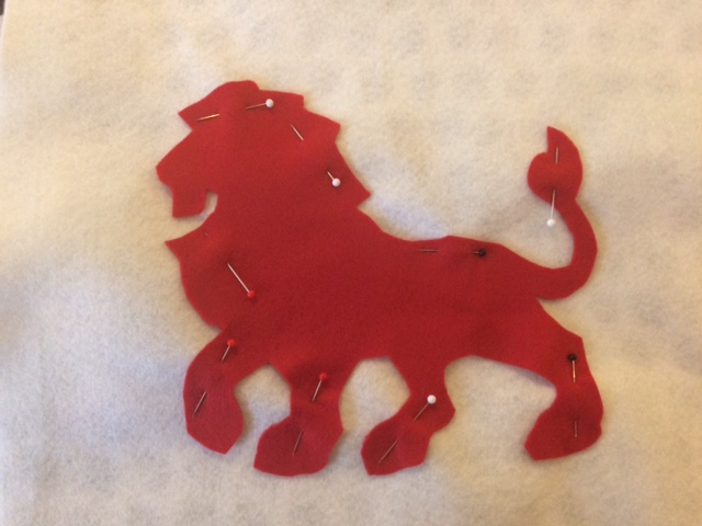 Red lion pinned to white felt