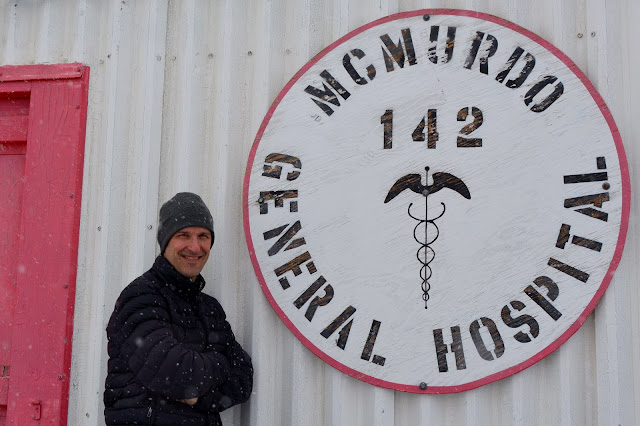 """A man stands next a building with a sign saying McMurdo General Hospital. Air Force Lt. Col. (Dr.) Tory Woodard, a USU School of Medicine class of 2001 alumnus, braves the snowfall outside the McMurdo General Hospital at McMurdo Station in Antarctica.  Woodard is finishing a 60-day deployment to the National Science Foundation site as part of """"Operation Deep Freeze.""""  The Joint Task Force-Support Forces Antarctica flight surgeon joined fellow USU alum, Dr. Christopher Martinez, class of 2007, the lead physician and clinic director at McMurdo, in Antarctica.  (Courtesy photo)"""