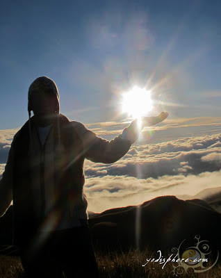 A Man holding the sun at Mt. Pulag Peak in Benguet