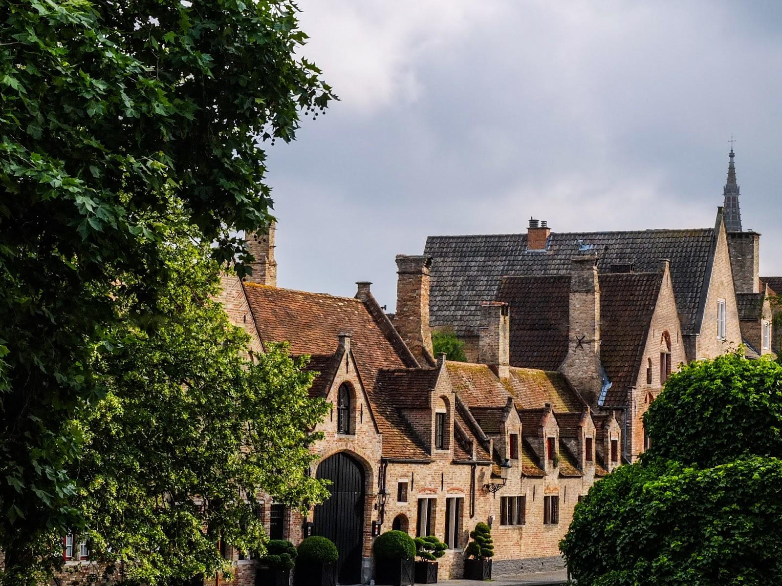 Ancient red brick buildings behind trees in Bruges, Belgium.