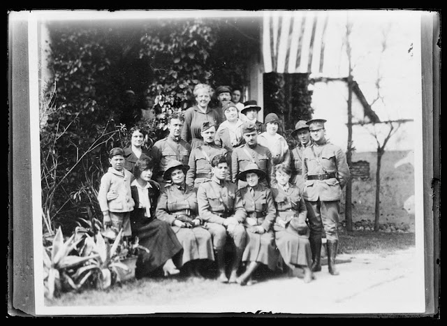 Red Cross personnel at Monastir. From left to right, back row, Miss Rogers and two Serb workers, next row, Miss Rose and Mrs. Freeman, next row: Serbian workers, Major Rogers Perkins, Captain Austin, Captain Pfotzer, Miss Crosley, Lieut., Paul Ivanichevitch, Lieut. Adams, front row, Serbian orphan, Miss Mountain, Dr. Keyes, Capt. Lanning McFarland, Dr. Flood, Miss Saxton. The two army officers in the group, Capts. Austin and Pfotzer organized the municipal health department of Monastir and are members of it. Drs. Keys and Flood, the two Red Cross women, have been the Balkans for a year and a half. During the Allied advance they worked in the front line dressing stations in the capacity of surgeons for days