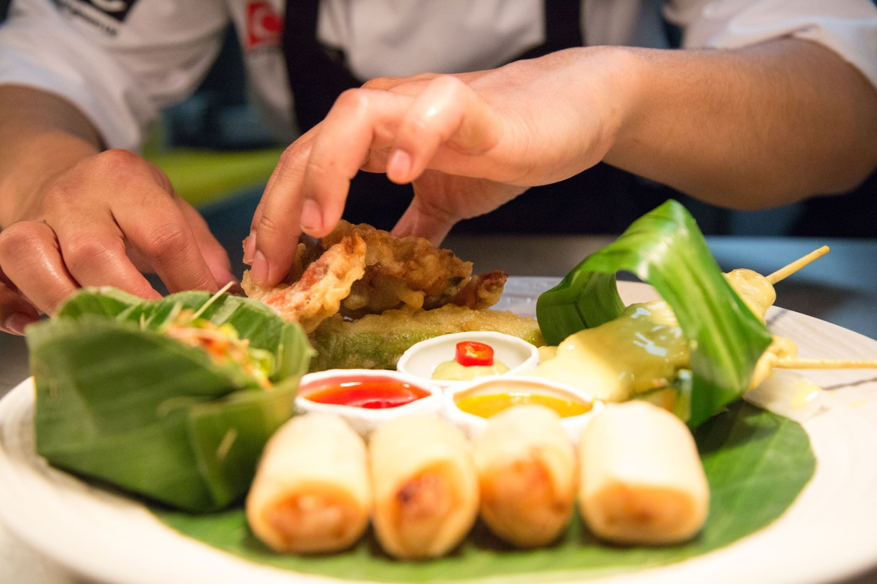 close up of spring rolls being made by someone on a white plate which has some red sauce