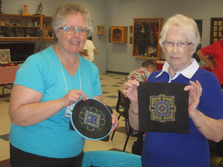 two women hold up their embroidery projects that are stitched on black fabric