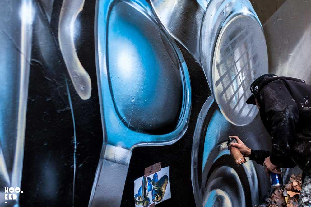 London street artist Fanakapan paints a mural in East London's Star Yard car park.