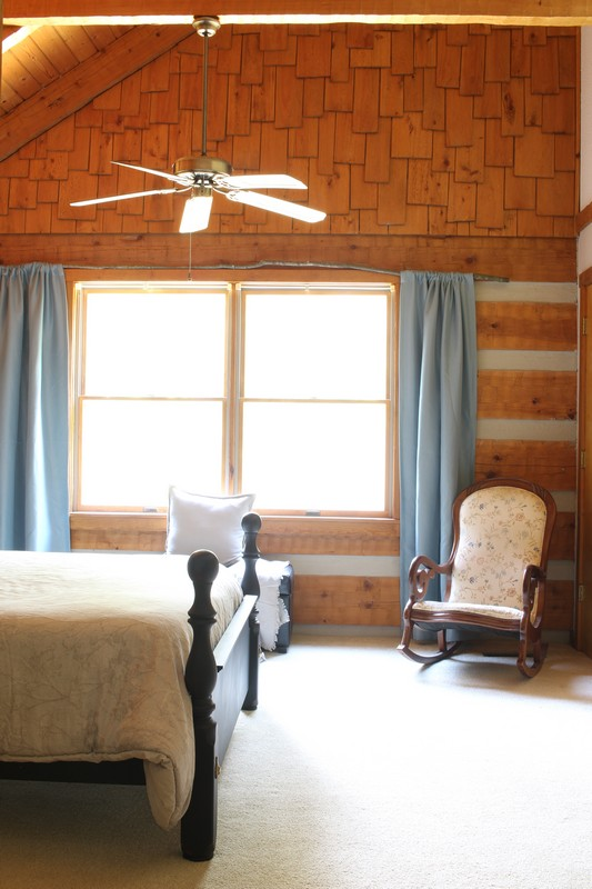 Log Cabin Bedroom with blue curtains and tree branch curtain rod