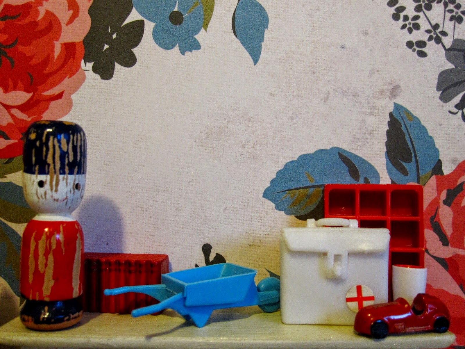 Selection of vintage miniature accessories displayed on a dolls' house mantlepiece. Colours are predominantly red, cream and mid=blue.