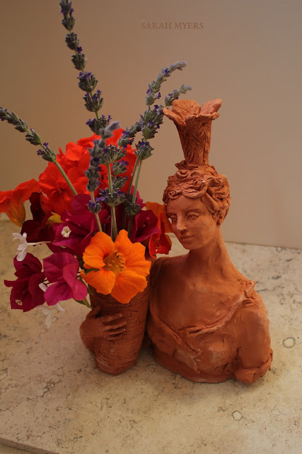 lady, plumes, basket, sarah, myers, art, arte, artist, terracotta, sculpture, vase, escultura, skulptur, flowers, bouquet, arrangement, beautiful, feathers, woman, figurative, decor, decorative, contemporary, modern, red, earthenware, clay, face, eyes, cornucopia, lavender, nasturtiums, jasmine, bougainvillea, spring, printemps, primavera, handmade, classical, bougainvillea, pink, yellow, serene