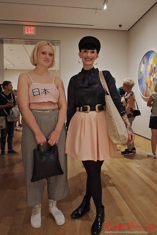 Two women at MOMA wearing pink and black outfits, hoop earing, fishermans cap, crop to, check trousers, pink skirt, creative eye make-up. Street Fashion Sydney New York Edition photographed by Kent Johnson.