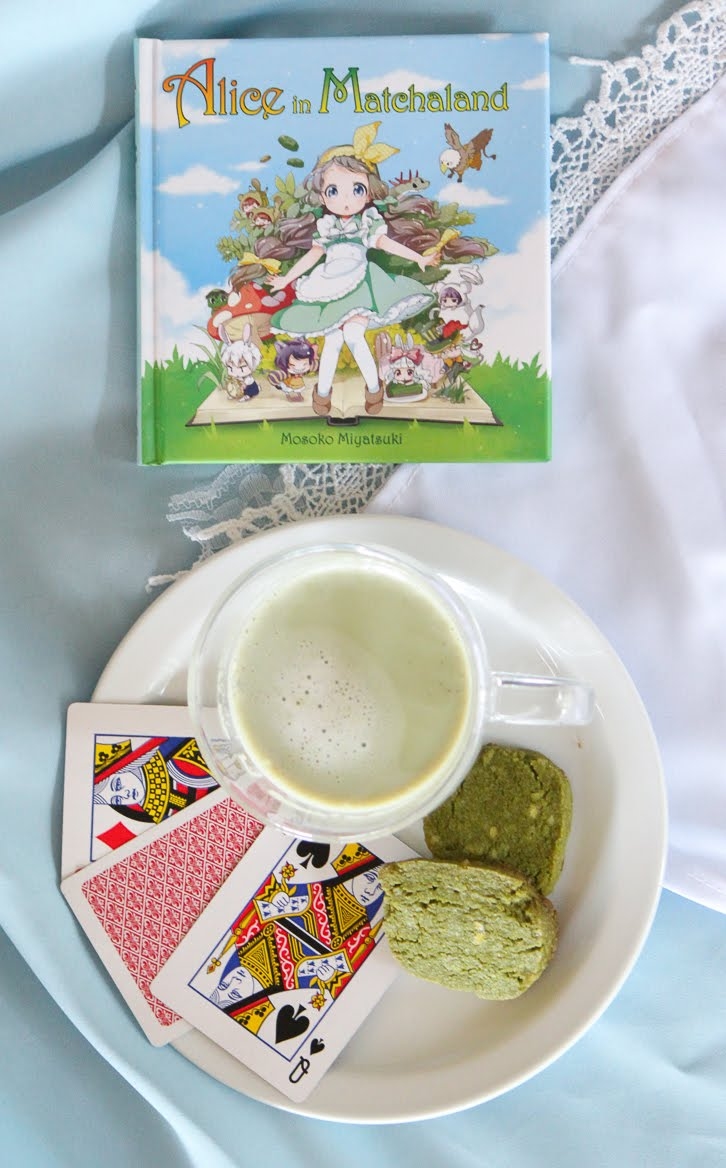 Top-down view of the manga cookbook Alice in Matchaland, with cookies, playing cards and glass teacup with matcha latte