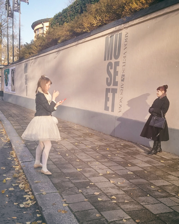 a lolita taking a picture of another lolita on the street