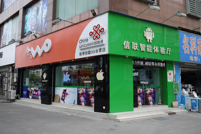 Store with China Unicom and Android signs plus some pillars with Apple logos
