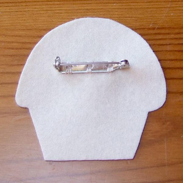 A hand sewn pinback clasp on cream felt backing fabric