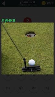 На поле для гольфа установлена лунка и клюшка приготовлена для игры